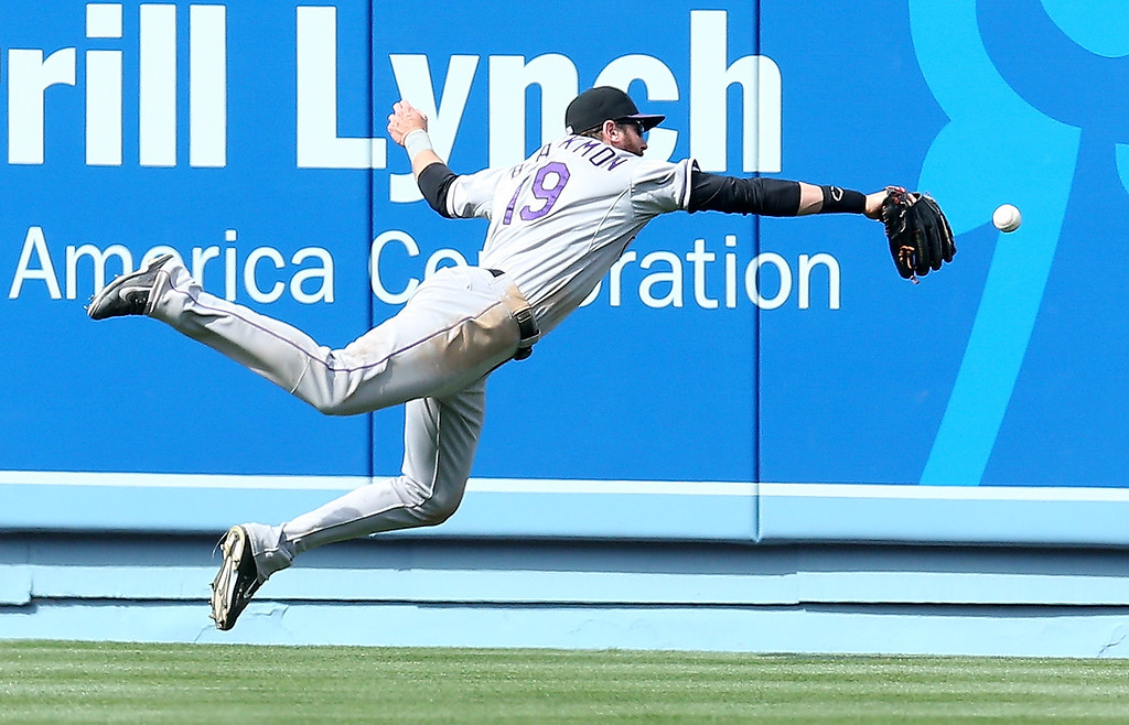 . Center fielder Charlie Blackmon #19 of the Colorado Rockies dives but can\'t catch a double hit by Matt Kemp of the Los Angeles Dodgers in the eighth inning at Dodger Stadium on April 27, 2014 in Los Angeles, California.  (Photo by Stephen Dunn/Getty Images)