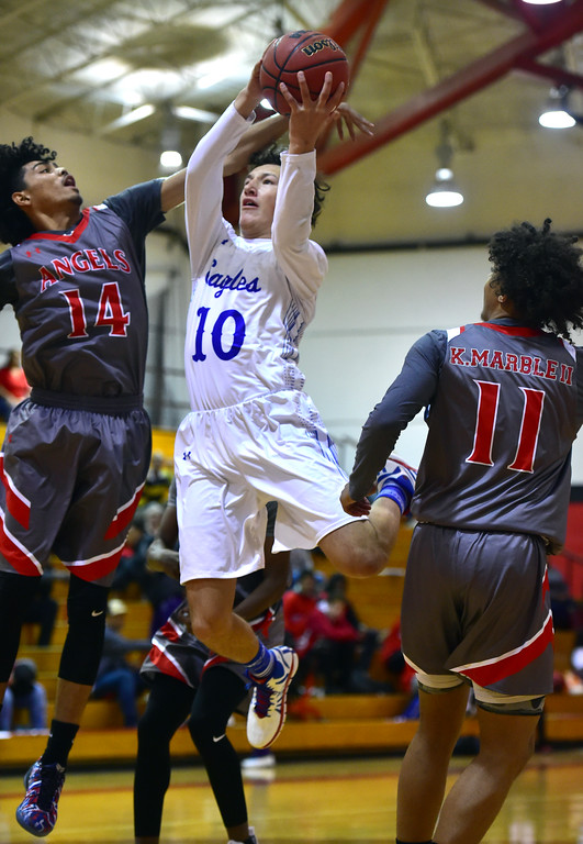 . Broomfield High School\'s Steven Croell drives to the basket against Denver East\'s Chase Neagle and Kwane Marble III during their game in the Fairview Festival on Wednesday. For More photos go to bocopreps.com Paul Aiken Staff Photographer Dec 6 2017