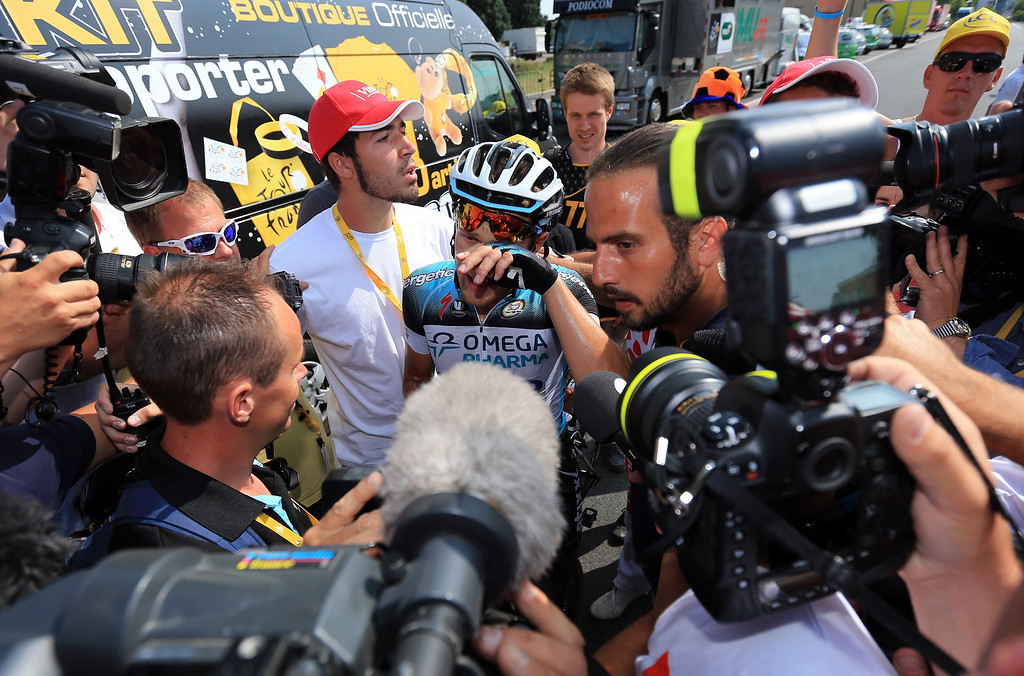 . LYON, FRANCE - JULY 13:  Matteo Trentin of Italy and Omega Pharma-Quickstep is mobbed by the media after winning stage fourteen of the 2013 Tour de France, a 191KM road stage from Saint-Pourcain-sur-Sioule to Lyon, on July 13, 2013 in Lyon, France.  (Photo by Doug Pensinger/Getty Images)