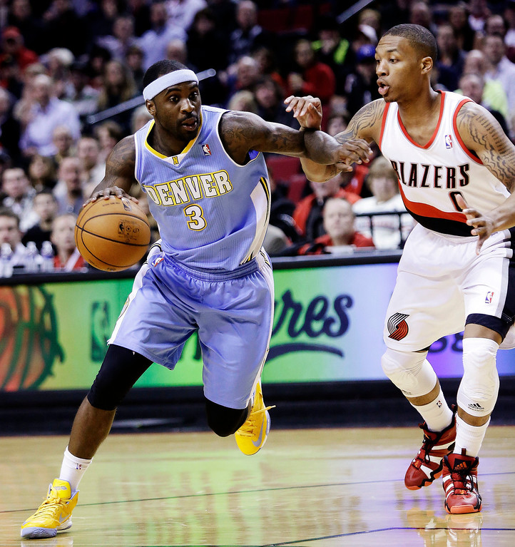 . Denver Nuggets guard Ty Lawson (3) drives inside against Portland Trail Blazers guard Damian Lillard during the first quarter of an NBA basketball game in Portland, Ore., Wednesday, Feb. 27, 2013. (AP Photo/Don Ryan)