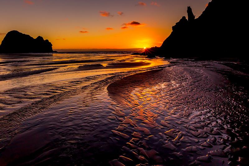 Sonnenuntergang an der Piha Beach