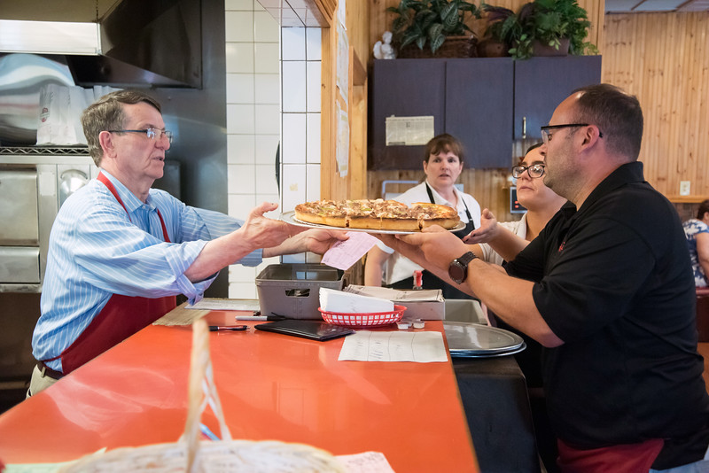 06/07/18  Wesley Bunnell | Staff  Owner of Central Pizza Jason Bikakis, L, hands a pizza to Berlin Police Officer Bob Canto to be brought to a table on June 7 in their annual Tip A Cop event.