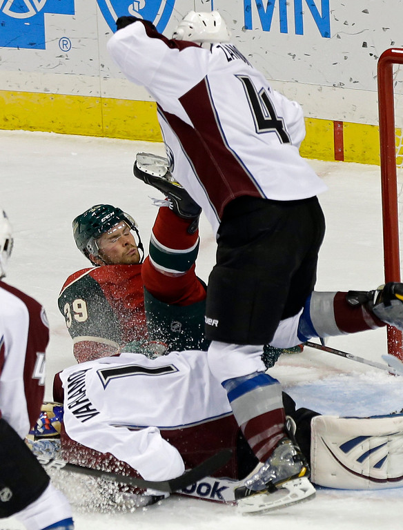 . Colorado Avalanche\'s Greg Zanon, right, sends Minnesota Wild\'s Nate Prosser  toppling over Avalanche goalie Semyon Varlamov of Russia, bottom, in the first period of an NHL hockey game Saturday, Jan. 19, 2013 in St. Paul, Minn.  (AP Photo/Jim Mone)