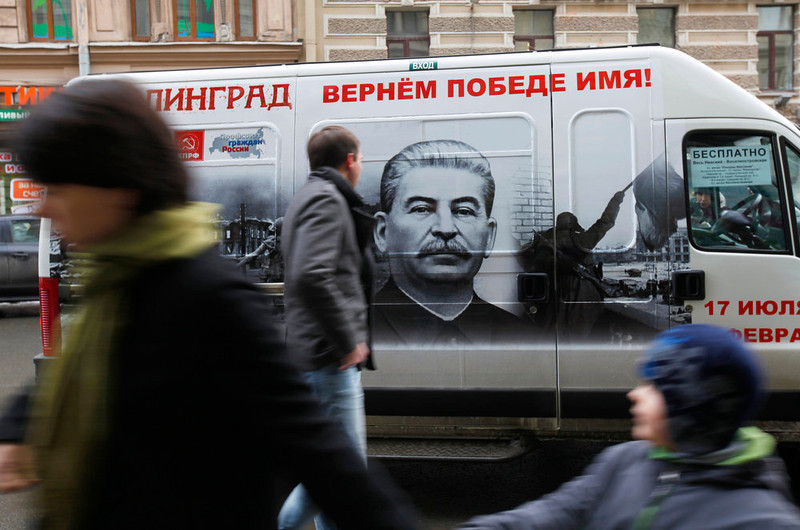 """. People walk by a bus adorned with a portrait of Soviet dictator Josef Stalin and a sign reading \""""Stalingrad gets back its victorious name\""""  in St. Petersburg, Russia on Feb. 2, 2013. An opinion survey commissioned by the Carnegie Endowment has revealed that Soviet dictator Josef Stalin has remained widely admired in Russia and other ex-Soviet nations despite his repressions that killed millions of people. It has found that support for Stalin in Russia has actually increased since the 1991 collapse of the Soviet Union.  (AP Photo/Elena Ignatyeva)"""