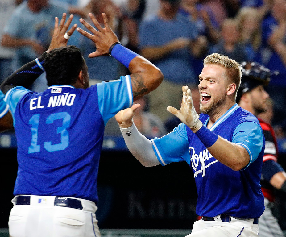 . Kansas City Royals\' Hunter Dozier, right, celebrates with Salvador Perez (13) after hitting a walk-off home run in a baseball game against the Cleveland Indians on Friday, Aug. 24, 2018, in Kansas City, Mo. The Royals won 5-4. (AP Photo/Charlie Riedel)