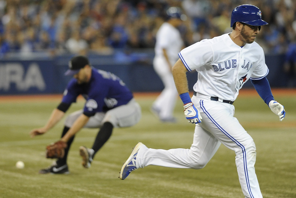 . J.P. Arencibia #9 of the Toronto Blue Jays runs to first as pitcher Matt Belisle #34 of the Colorado Rockies fields the ball during inter-league MLB game action June 17, 2013 at Rogers Centre in Toronto, Ontario, Canada. (Photo by Brad White/Getty Images)