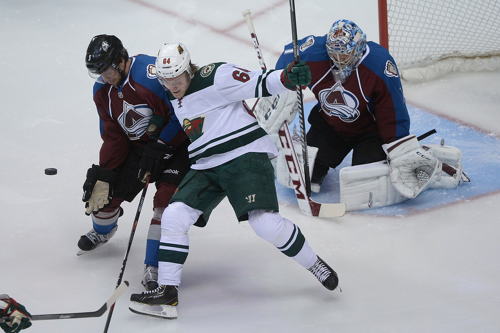 . DENVER, CO - APRIL 26: Mikael Granlund (64) of the Minnesota Wild and Nate Guenin (5) of the Colorado Avalanche battle for the puck as Semyon Varlamov (1) tends the net during the first period. The Colorado Avalanche hosted the Minnesota Wild during game five of the first round of the NHL Stanley Cup Playoffs at the Pepsi Center on Saturday, April 26, 2014. (Photo by Karl Gehring/The Denver Post)