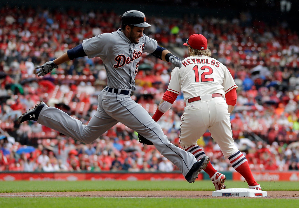 . Detroit Tigers\' J.D. Martinez, left, is safe at first as St. Louis Cardinals first baseman Mark Reynolds looks for the throw during the first inning of a baseball game Saturday, May 16, 2015, in St. Louis. (AP Photo/Jeff Roberson)