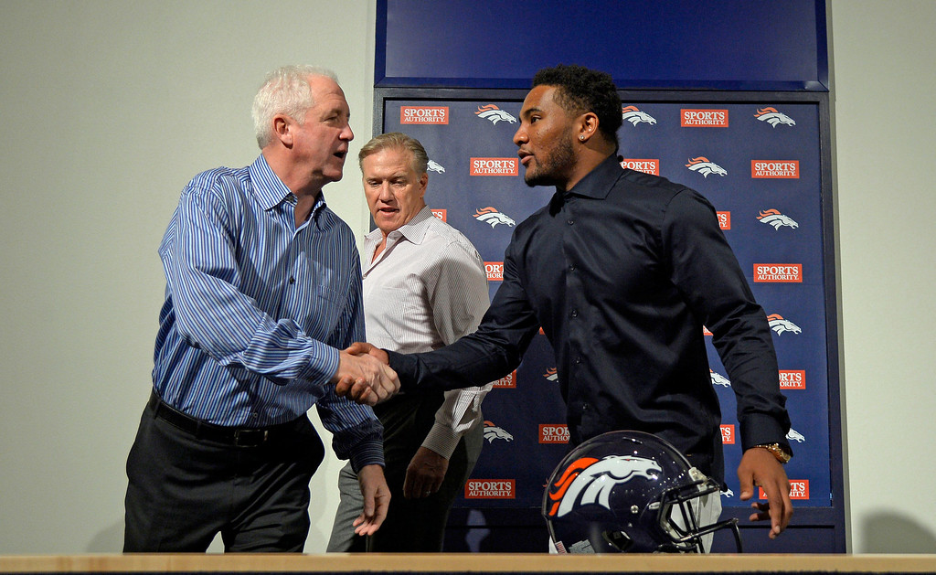 . Denver Broncos head coach John Fox shakes hand with T.J. Ward and John Elway, General Manager and Executive Vice President of Football Operations pose for a photo after a press conference March 12, 2014 at Dove Valley. The Broncos have agreed to terms with former Cleveland Browns strong safety T.J. Ward, who is coming off a Pro Bowl season. Ward will sign a four-year contract for $23 million � with $14 million guaranteed. (Photo by John Leyba/The Denver Post)