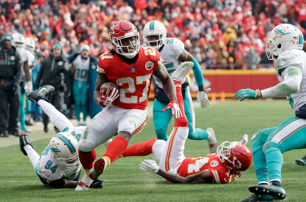 . Kansas City Chiefs running back Kareem Hunt (27) carries the ball away from Miami Dolphins linebacker Lawrence Timmons (94) during the first half of an NFL football game in Kansas City, Mo., Sunday, Dec. 24, 2017. (AP Photo/Charlie Riedel)