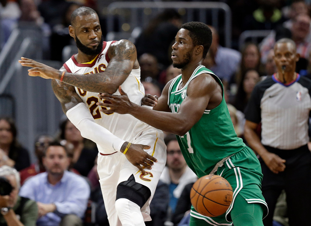 . Cleveland Cavaliers\' LeBron James, left, passes against Boston Celtics\' Semi Ojeleye in the first half of an NBA basketball game, Tuesday, Oct. 17, 2017, in Cleveland. (AP Photo/Tony Dejak)