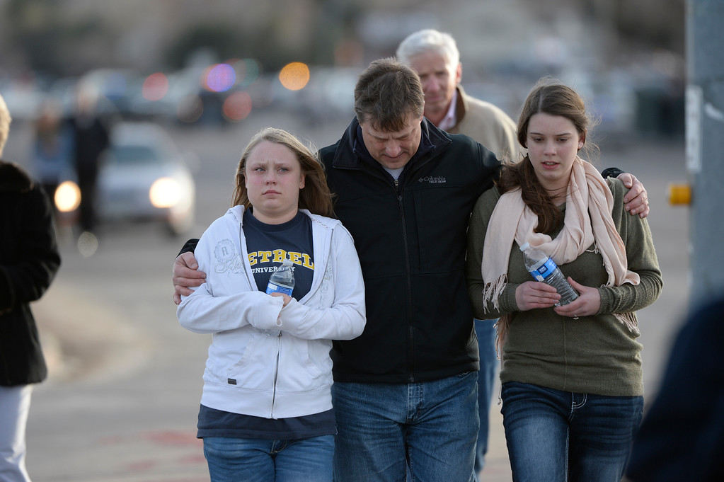""". CENTENNIAL, CO. - DECEMBER 13: Todd Skodda walks with his daughters, Emily, 18, left and Abby, 16,at Arapahoe High School in Centennial, CO December 13, 2013. A student who carried a shotgun into Arapahoe High School and asked where to find a specific teacher opened fire on Friday, wounding two fellow students before apparently killing himself, Arapahoe County Sheriff Grayson Robinson said. Abby said she hid in her in Chemistry class when the shooting stated, \""""all we did was pray, \'God deliver us,\' and he did.\"""" (Photo By Craig F. Walker / The Denver Post)"""
