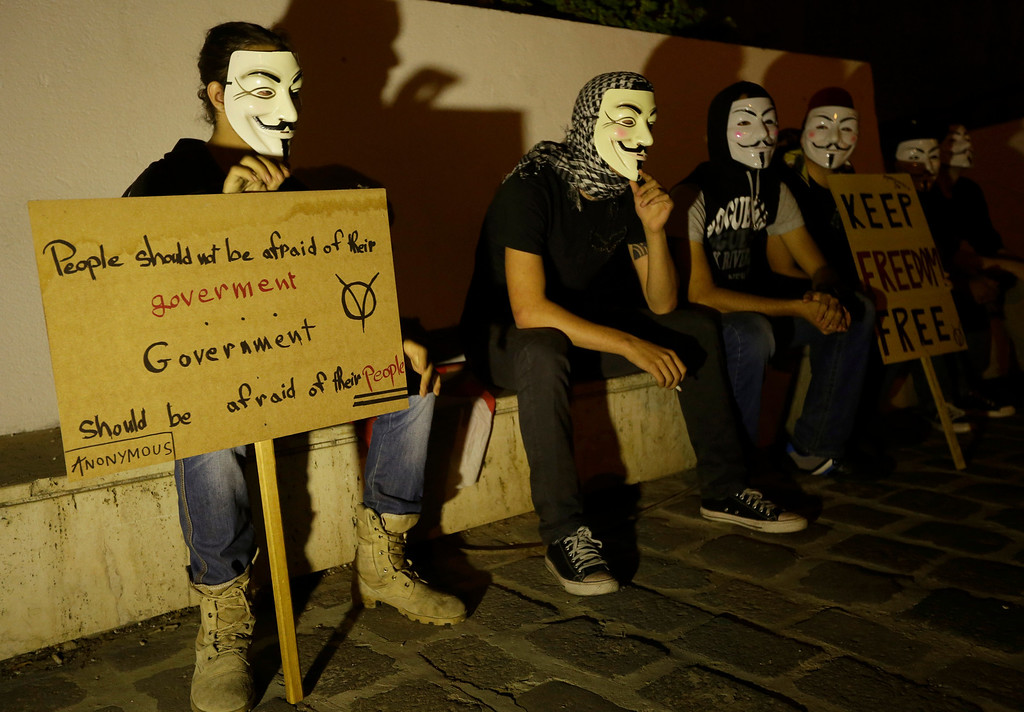 . Lebanese activists wear masks and hold placards, protest against corrupt governments and corporations, in support of the anonymous activist moment, at the Martyrs square, in downtown Beirut, Lebanon, Tuesday, Nov 5, 2013, as part of a Million Mask March of similar rallies around the world on Guy Fawkes Day. (AP Photo/Hussein Malla)