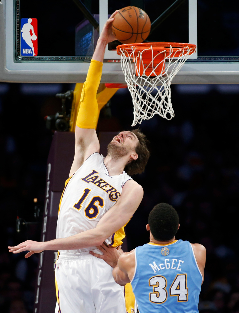 . Los Angeles Lakers\' Pau Gasol of Spain dunks the ball over Denver Nuggets\' JaVale McGee during the first half of their NBA basketball game in Los Angeles January 6, 2013. REUTERS/Danny Moloshok
