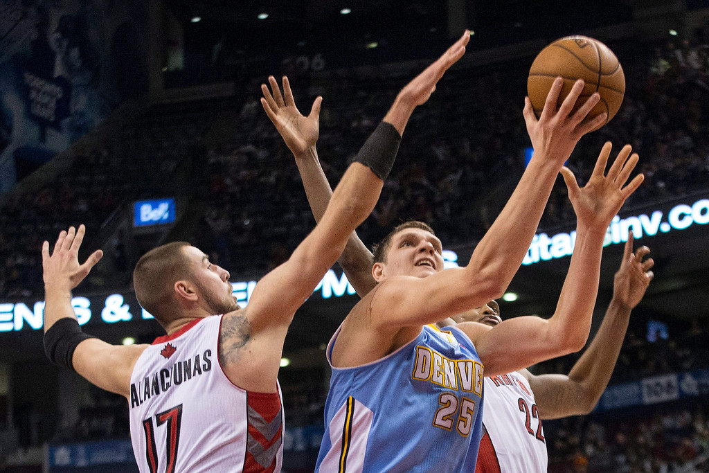 . Denver Nuggets\' Timofey Mozgo, center, shoots as Toronto Raptors\' Jonas Valanciunas, left, and Rudy Gay defend during the second half of an NBA basketball game on Sunday, Dec. 1, 2013, in Toronto. (AP Photo/The Canadian Press, Chris Young)