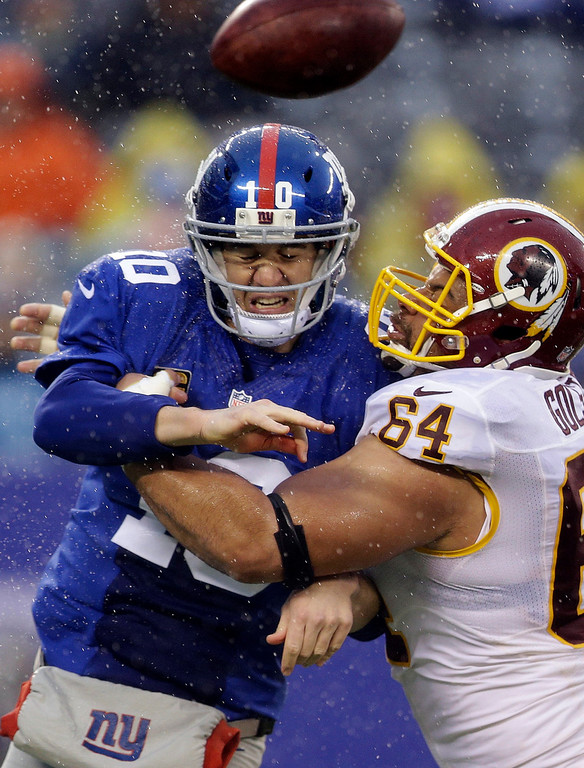 . Washington Redskins defensive end Kedric Golston (64) hits New York Giants\' Eli Manning (10) who throws a pass during the first half of an NFL football game on Sunday, Dec. 29, 2013, in East Rutherford, N.J. (AP Photo/Julio Cortez)
