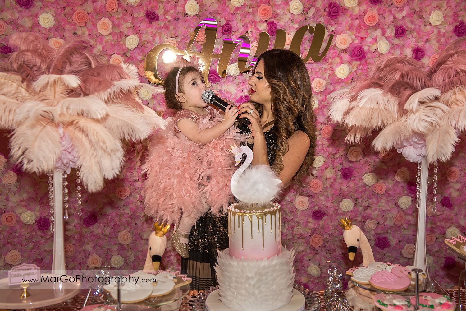 little girl in pink feather dress singing to mic on the pink and white flower wall at Newark Oasis Palace
