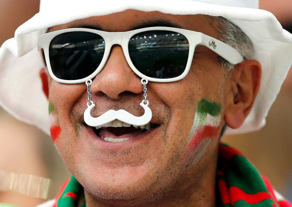 . An Iranian fan wears a fake mustache before the group F World Cup soccer match between Iran and Nigeria at the Arena da Baixada in Curitiba, Brazil, Monday, June 16, 2014.  (AP Photo/Frank Augstein)