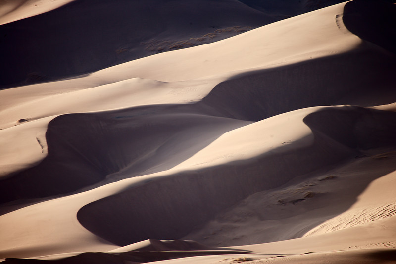 Sand dunes slopes and valleys form abstract designs.