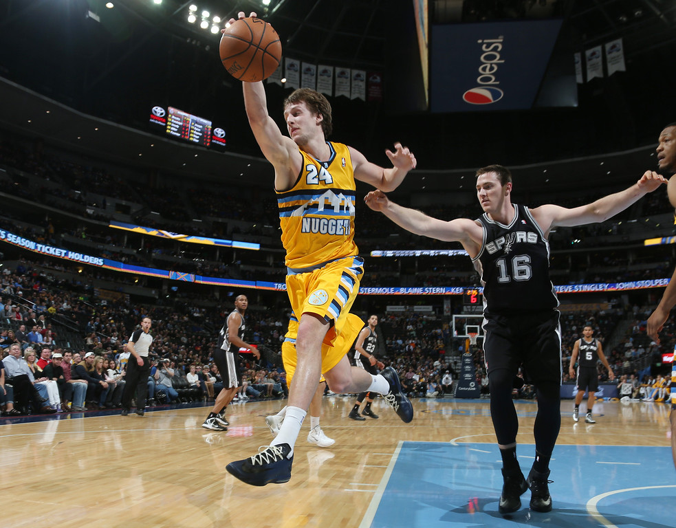 . Denver Nuggets forward Jan Vesely, front, of the Czech Republic, reaches to pull in a loose ball as San Antonio Spurs forward Aron Baynes covers in the fourth quarter of the Spurs\' 133-102 victory in an NBA basketball game in Denver, Friday, March 28, 2014. (AP Photo/David Zalubowski)