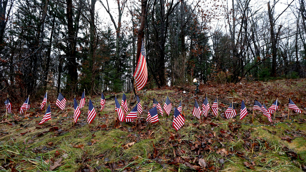 Description of . Twenty-seven small U.S. flags adorn a large flag on a makeshift memorial on the side of Highway 84 near the Newtown, Conn., town line as residents mourn victims killed by gunman Adam Lanza, Monday, Dec. 17, 2012. On Friday, authorities say Lanza killed his mother at their home and then opened fire inside the Sandy Hook Elementary School in Newtown, killing 26 people, including 20 children, before taking his own life. (AP Photo/Julio Cortez)