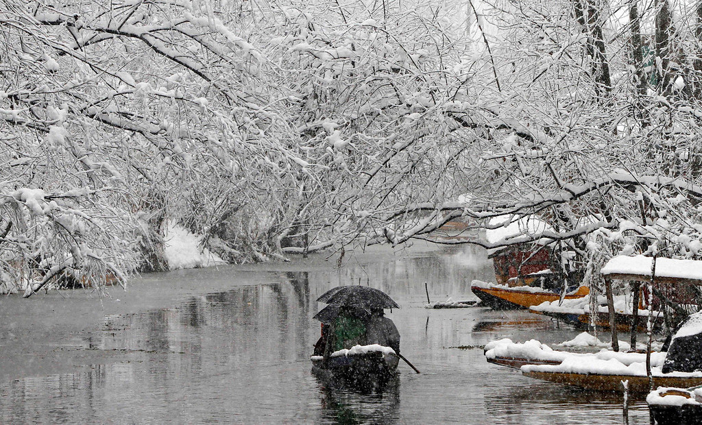 . A boat filled with passengers move on the Dal Lake during snowfall in Srinagar, India, Tuesday, Dec. 31, 2013. Snowfall in the Indian portion of Kashmir has disrupted power supply,air traffic and road traffic between Srinagar and Jammu, the summer and winter capitals of India\'s Jammu-Kashmir state, according to news reports. (AP Photo/Mukhtar Khan)