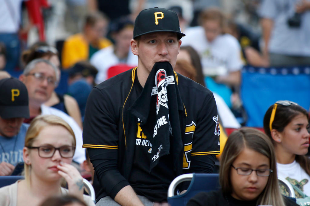 . Pittsburgh Pirates fan Jimmy Cich of Toronto, Ohio, bites on a Pirates rally towel as he sits with hundreds of others who gathered outside PNC Park in Pittsburgh to watch on a large television showing the broadcast of Game 1 of the National League division series in St. Louis between the Pirates and the St. Louis Cardinals, Thursday, Oct. 3, 2013. (AP Photo/Keith Srakocic)