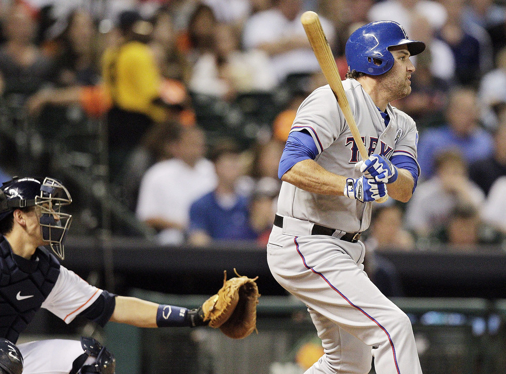 . Lance Berkman #27 of the Texas Rangers singles to center field in the fourth inning against the Houston Astros on Opening Day at Minute Maid Park on March 31, 2013 in Houston, Texas.  (Photo by Bob Levey/Getty Images)