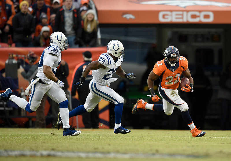 . C.J. Anderson (22) of the Denver Broncos makes a run in the first quarter while being pursued by Mike Adams (29) of the Indianapolis Colts and LaRon Landry (30) of the Indianapolis Colts. The Denver Broncos played the Indianapolis Colts in an AFC divisional playoff game at Sports Authority Field at Mile High in Denver on January 11, 2015. (Photo by John Leyba/The Denver Post)