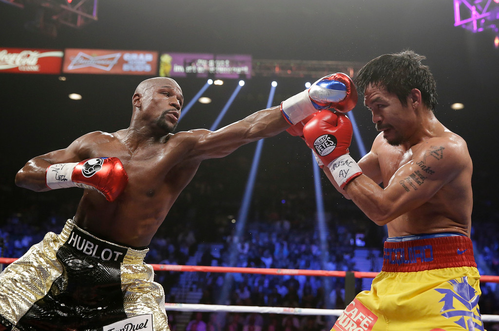 . Floyd Mayweather Jr., left, trades blows with Manny Pacquiao, from the Philippines, during their welterweight title fight on Saturday, May 2, 2015 in Las Vegas. (AP Photo/Isaac Brekken)