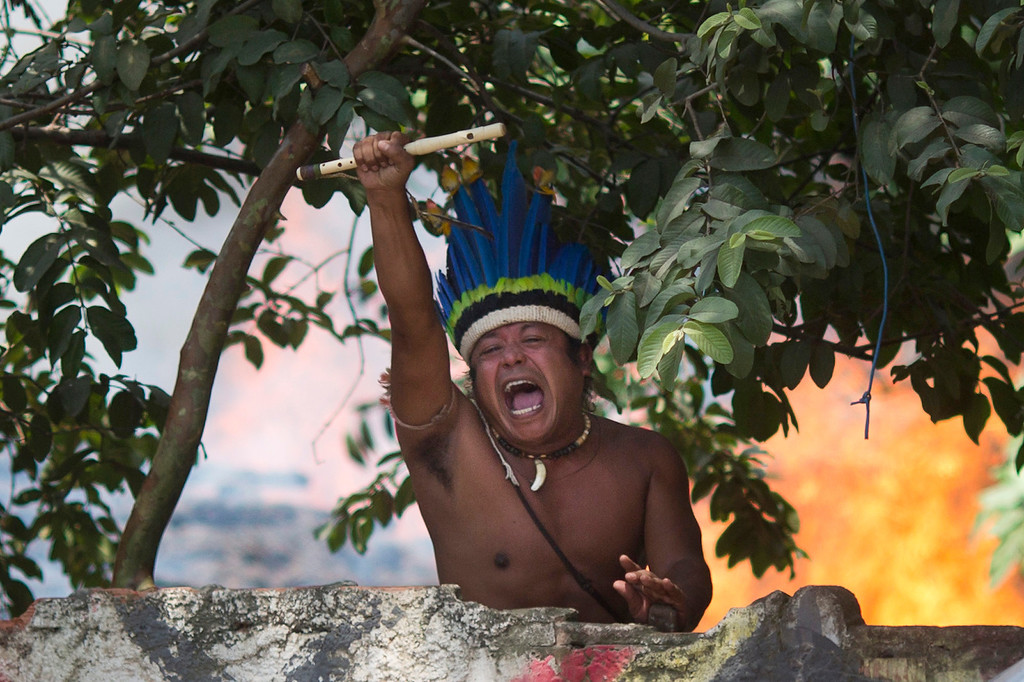 . An indigenous man shouts to police, clutching a flute from inside the old Indian Museum where a fire burns behind in Rio de Janeiro, Friday, March 22, 2013. Police in riot gear invaded an old Indian museum complex Friday and pulled out a few dozen indigenous people who for months resisted eviction from the building, which will be razed as part of World Cup preparations next to the legendary Maracana football stadium. (AP Photo/Felipe Dana)