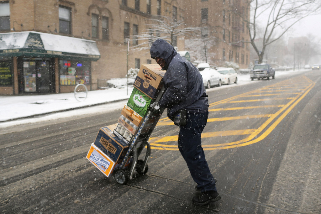 . A delivery man navigates the streets in the snow on March 8, 2013 in the Brooklyn borough of New York City. (Photo by Spencer Platt/Getty Images)