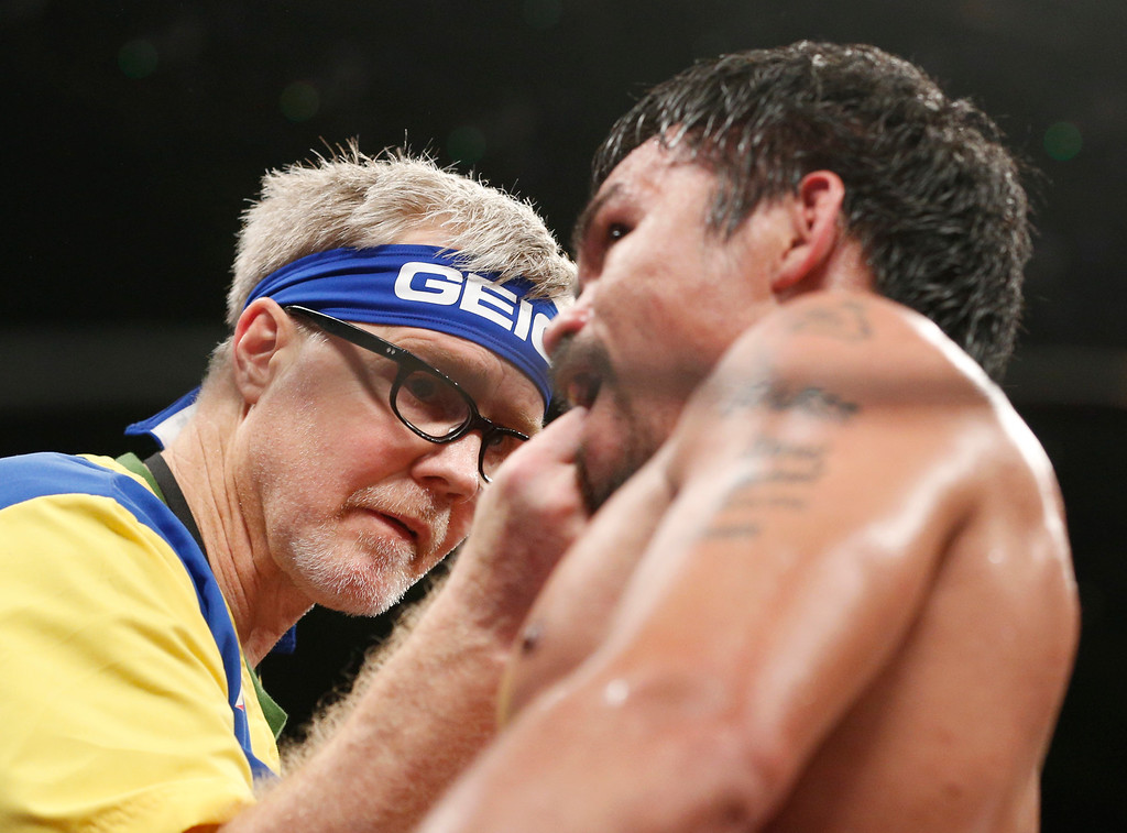 . Trainer Freddie Roach, left, checks on Manny Pacquiao, from the Philippines, during their welterweight title fight against Floyd Mayweather Jr. on Saturday, May 2, 2015 in Las Vegas. (AP Photo/John Locher)