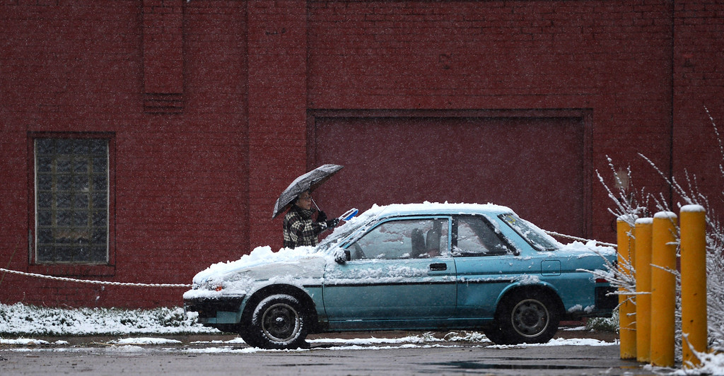 . Sara Romero clears snow from her car in Denver, May 01, 2013. (Photo By RJ Sangosti/The Denver Post)