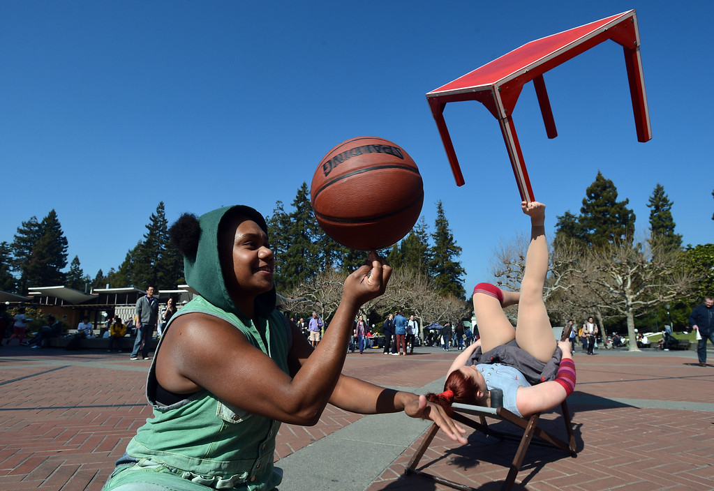 """. Circus Oz performer Hazel Bock juggles a card table with her feet while Ghenoa Gela spins a basketball as the Australian circus group performs on Sproul Plaza at the University of California to preview their new show \""""From the Ground Up\"""" in Berkeley, Calif. on Wednesday, Feb. 13, 2013. Presented by Cal Performances, Circus Oz will perform at Zellerbach Hall Friday Feb. 15 at 8 pm, Sat. Feb 16 at 2 pm and Sun. Feb 17 at 3 pm. (Kristopher Skinner/Staff)"""
