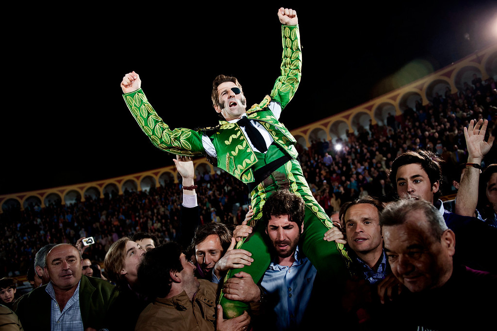 . In this March 4, 2012 photo, Spanish bullfighter Juan Jose Padilla is carried out of the ring among jubilant crowd scenes on the shoulders of fellow bullfighter Serafin Marin, a honor for the best performers, after a bullfight at the southwestern Spanish town of Olivenza. This photo is one in a series of images by Associated Press photographer Daniel Ochoa de Olza that won the second place prize for the Observed Portrait series category in the World Press Photo 2013 photo contest.  (AP Photo/Daniel Ochoa de Olza, File)