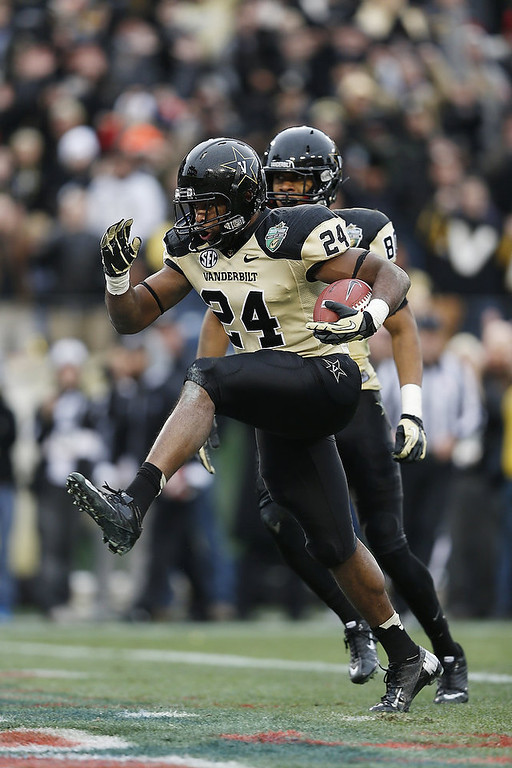 . Wesley Tate #24 of the Vanderbilt Commodores high-steps into the end zone for a seven-yard touchdown run against the North Carolina State Wolfpack during the Franklin American Mortgage Music City Bowl at LP Field on December 31, 2012 in Nashville, Tennessee. (Photo by Joe Robbins/Getty Images)