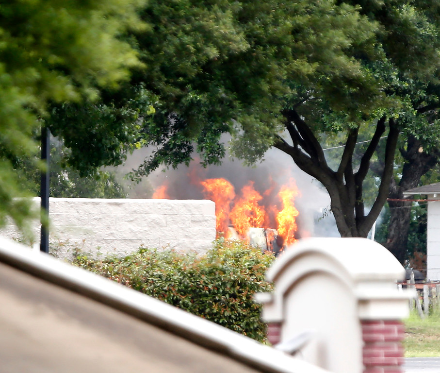 . The armored van used by a lone shooter to attack and then flee Dallas Police Headquarters catches fire outside a fast food restaurant on June 13, 2015 in Hutchins, Texas. Authorities used controlled charges to discharge pipe bombs in the van after the shooter reportedly unleashed multiple rounds and planted explosive devices around the station before leading police on a chase that ended in a standoff in the parking lot of a fast food restaurant. (Photo by Stewart F. House/Getty Images)