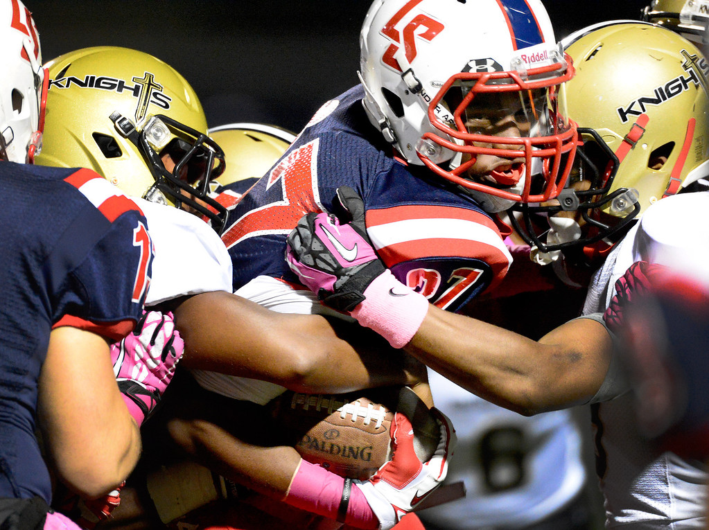 . La Salle\'s running back Milan Acquaah (27) is tackled by Bishop Montgomery during the first quarter in Friday night\'s football game at La Salle High School in Pasadena, October 25, 2013.  (Photo by Sarah Reingewirtz/Pasadena Star-News)