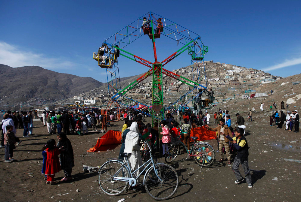 . Children play on a ferris wheel during a gathering to celebrate the Afghan New Year (Nawroz) in Kabul March 21, 2013. Nawroz, also known as Persian New Year, is observed during the March equinox, marking the first day of spring. REUTERS/Mohammad Ismail