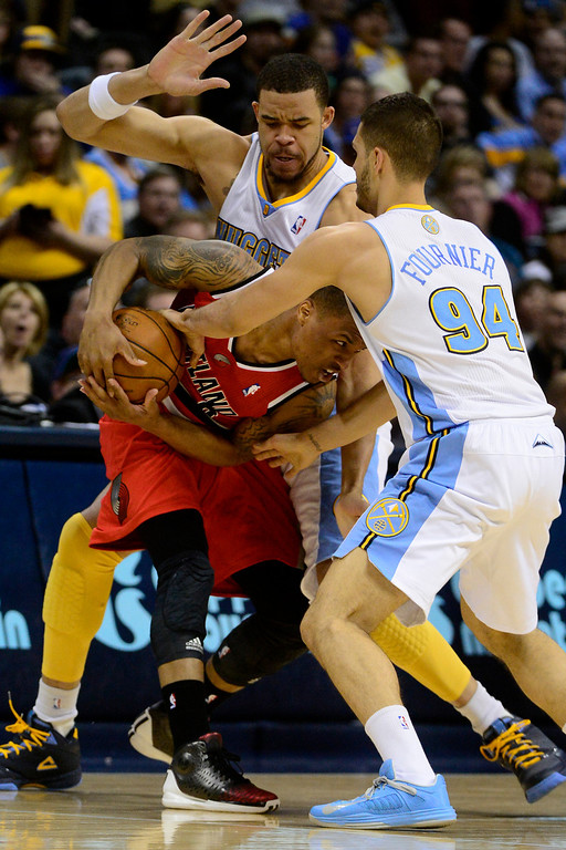 . DENVER, CO - APRIL 14: JaVale McGee (34) of the Denver Nuggets and Evan Fournier (94) of the Denver Nuggets defend Damian Lillard (0) of the Portland Trail Blazers during the first half of action. The Denver Nuggets play the Portland Trail Blazers at the Pepsi Center. (Photo by AAron Ontiveroz/The Denver Post)