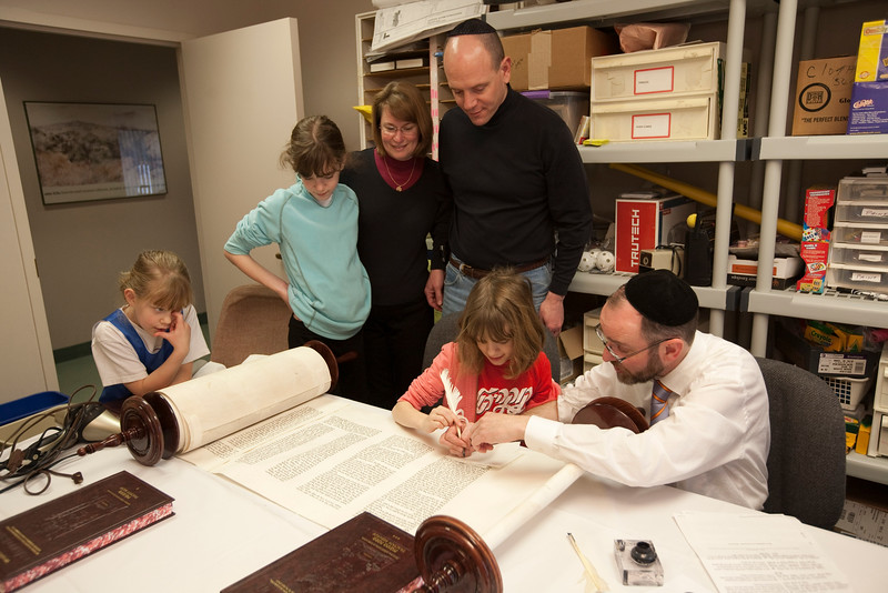 Sofer (Torah scribe) and Rabbi Menachem Youlus helps a family fill in letters