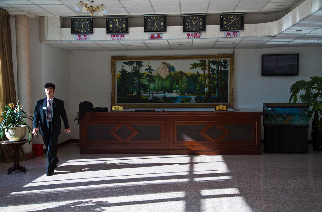 """. In this June 19, 2014 photo, a hotel employee walks in the lobby of a hotel that accommodates foreign visitors in Chongjin, North Korea. The Associated Press was granted permission to embark on a weeklong road trip across North Korea to the countryís spiritual summit Mount Paektu. The trip was on North Korea\'s terms. An AP reporter and photographer couldn\'t interview ordinary people or wander off course, and government \""""minders\"""" accompanied them the entire way. (AP Photo/David Guttenfelder)"""