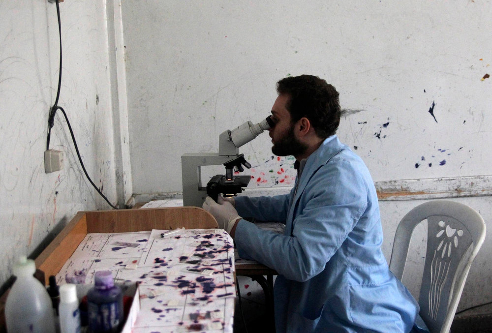 Description of . A medical laboratory technician views blood samples from patients showing symptoms of leishmaniasis through a microscope at a hospital in Aleppo, February 11, 2013. Doctors in Aleppo and Deir al-Zor have reported outbreaks of leishmaniasis, an endemic tropical disease transmitted by sand-flies that causes skin ulcers resembling leprosy, the World Health Organization (WHO) said. Poor waste management and lack of hygiene have fuelled its spread, but the U.N. agency is trying to deliver medicines to both hotspots, WHO spokesman Glenn Thomas told a news briefing. REUTERS/Muzaffar Salman