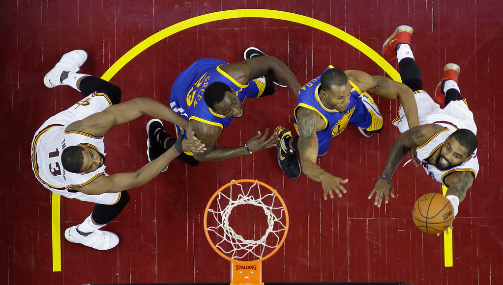 . Cleveland Cavaliers guard Kyrie Irving (2) shoots on Golden State Warriors forward Andre Iguodala, second from right, during the first half of Game 4 of basketball\'s NBA Finals in Cleveland, Friday, June 9, 2017. (AP Photo/Ron Schwane, Pool)