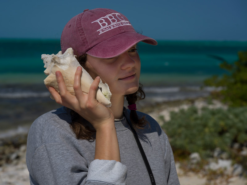 Woman holding conch shell close to her ear, Half Moon Caye, Lighthouse Reef Atoll, Belize
