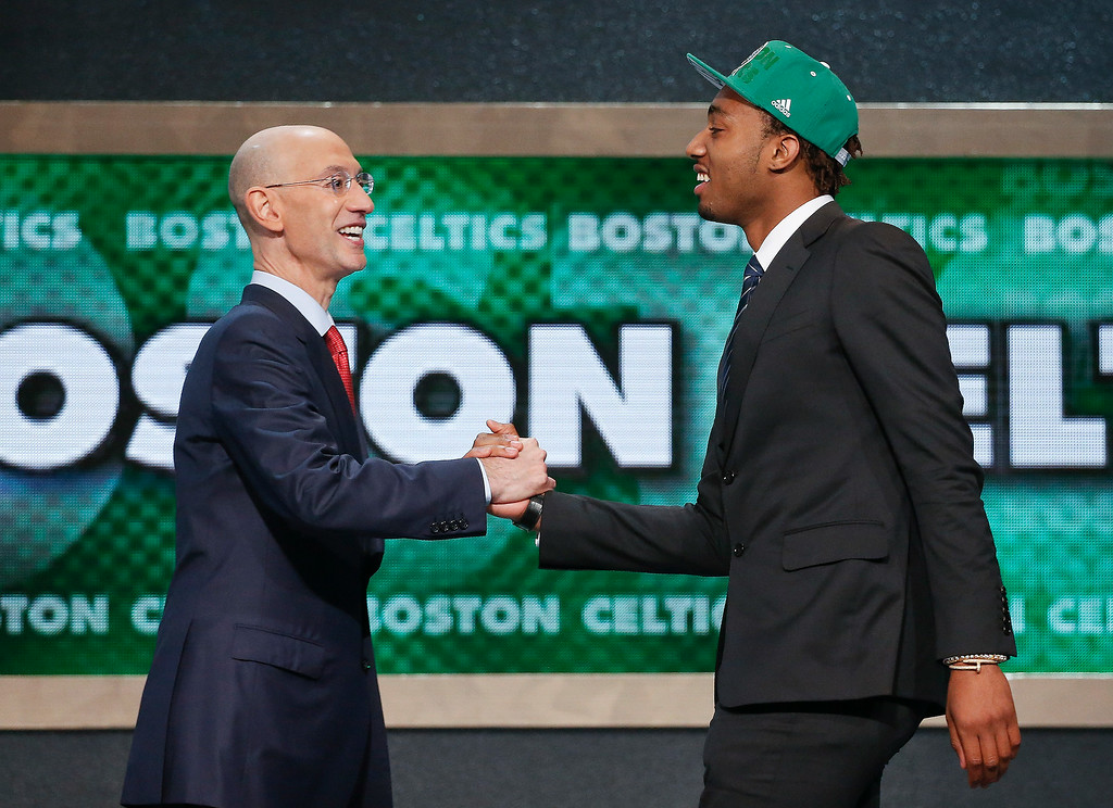 . Kentucky\'s James Young, right, is greeted by NBA Commissioner Adam Silver after being selected as the 17th overall pick by the Boston Celtics during the 2014 NBA draft, Thursday, June 26, 2014, in New York. (AP Photo/Jason DeCrow)