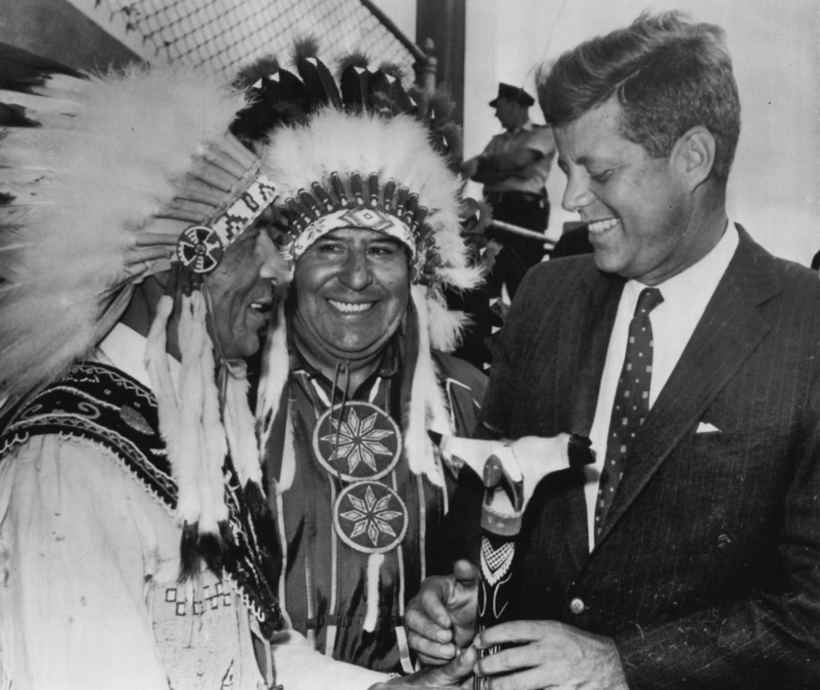 . Sen. Kennedy receives a gift war club from Joseph Ranco, left, of the Penobscot tribe and Bruce Poolaw in September 1960 during a campaign tour of Maine.  Denver Post file