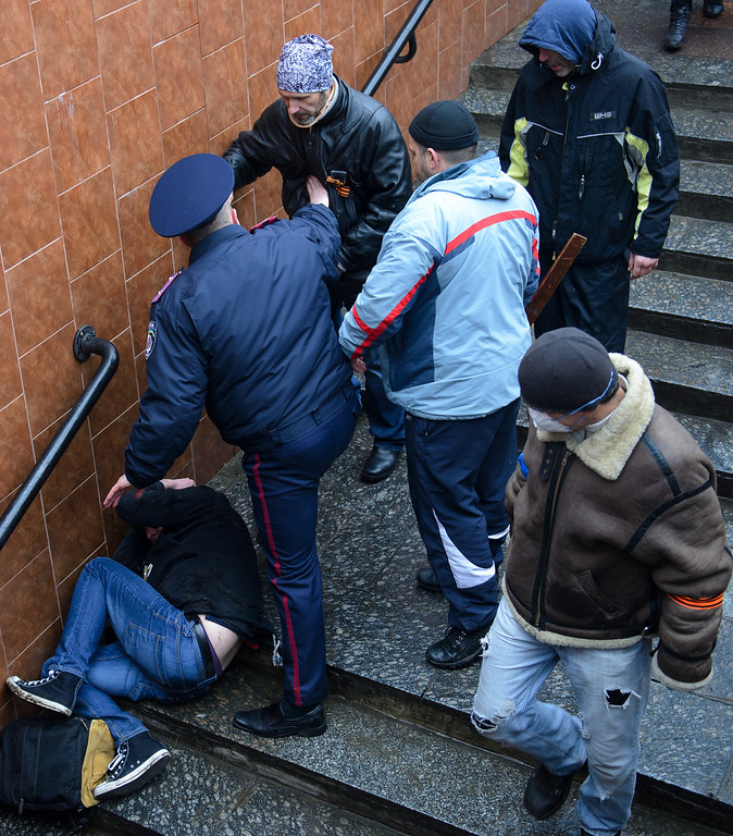 . A Ukrainian police officer is stops a pro-Russian activist who is charging to beat the Ukrainian protester lying on the steps in Kharkiv, Ukraine, Sunday, April 13, 2014.  Two rival rallies in Kharkiv turned violent after a group of pro-Russian protesters followed several pro-Ukrainian activists, beating them with baseball bats and sticks. (AP Photo/ Olga Ivashchenko)