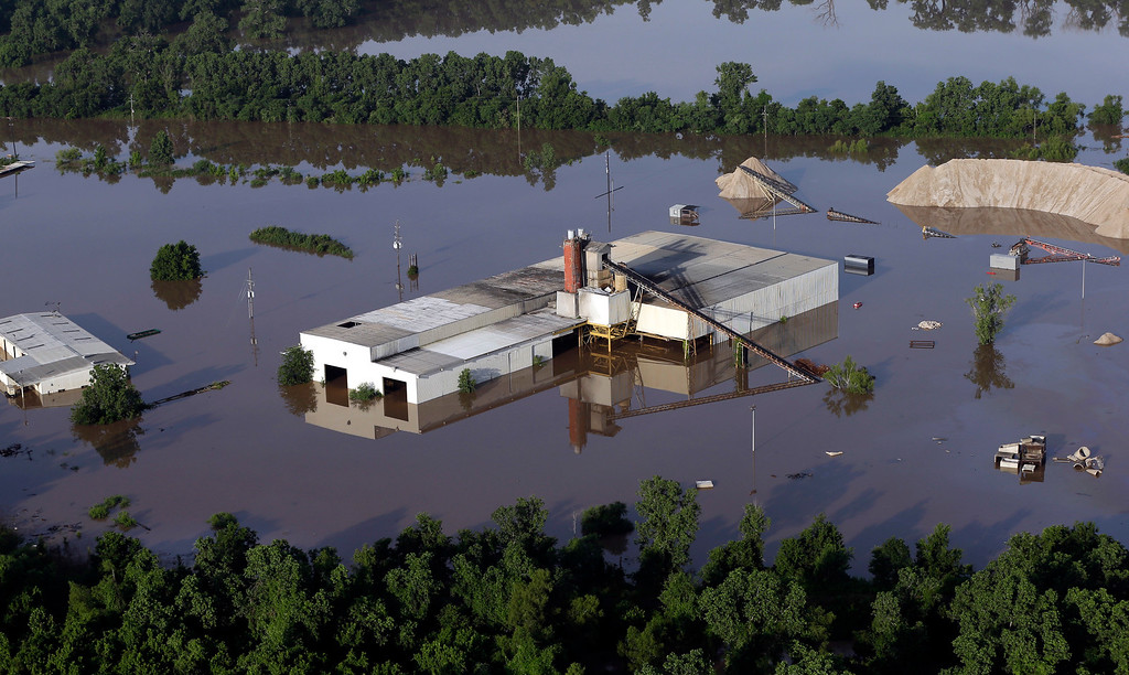 . In this aerial photo, a business is flooded near the Brazos River Saturday, May 30, 2015, in Sugar Land, Texas. The Colorado River in Wharton and the Brazos and San Jacinto rivers near Houston are the main focus of concern as floodwaters moved from North and Central Texas downstream toward the Gulf of Mexico. (AP Photo/David J. Phillip)